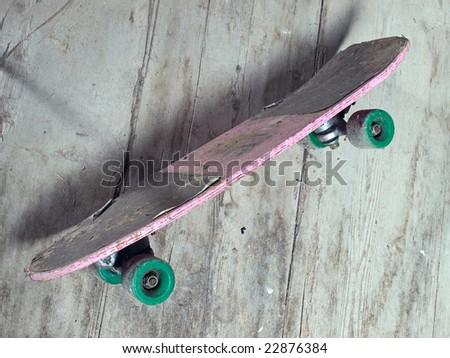 Old battered skateboard in grunge style.