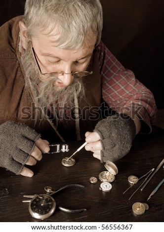 Old bearded man reparing antique watches using a magnifying glass