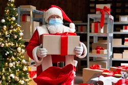 Old bearded Santa Claus wearing costume, face mask, holding present gift box packing in sack bag preparing for xmas eve in workshop. Merry Christmas Covid 19 coronavirus safe delivery concept.