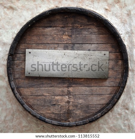 Old beer barrel with metal plate