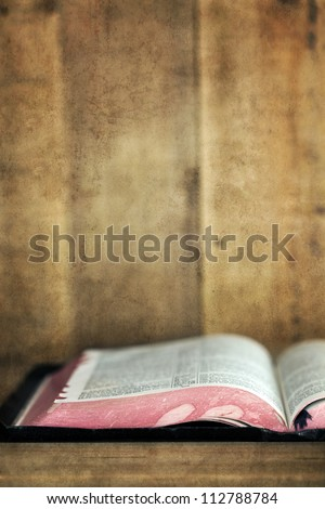 Old Bible, open on a wooden bookshelf.  With grunge effects.