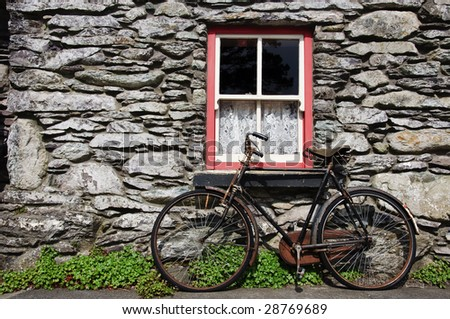 old bicycle by rural cottage wall