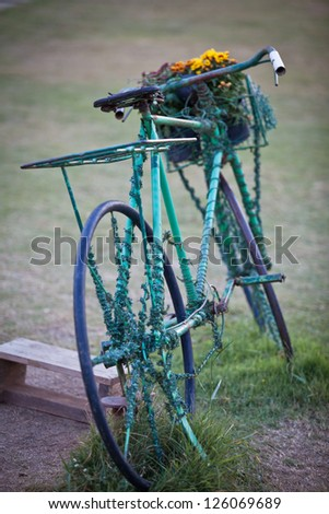 Old bicycle decorate with flowers stand in the garden