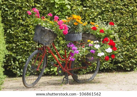 old bicycle equipped with baskets of flowers