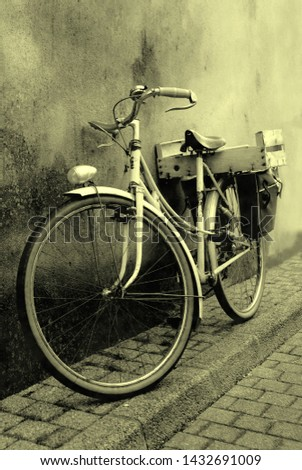 Old bicycle lying against a wall in sepia color