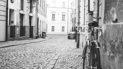 Old bicycle parked in street. Bike leaning on a wall. Historical city center.