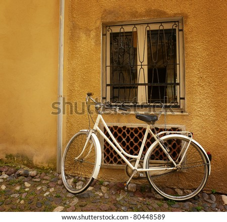Old bicycle standing against a wall under a window.