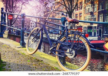 Old bicycle standing next to canal. Amsterdam cityscape
