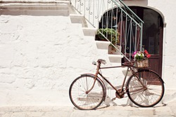 Old bicycle with a basket leaning against a wall in Italy