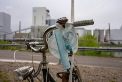 Old bicycle with a collection of mouth-nose protectors on the handlebars and industrial building in the background. Waste during COVID-19.