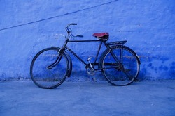 Old bike next to a blue wall