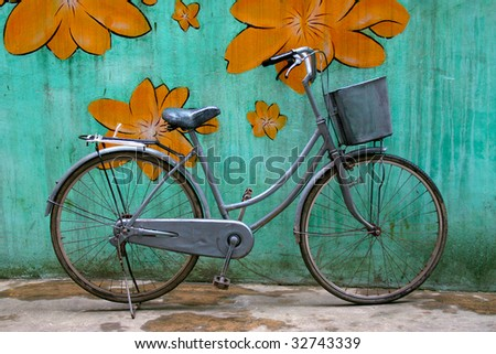 Old bike with a basket against a colourful wall.