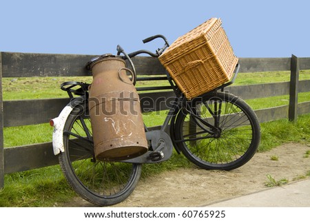 Old bike with milk can and bakery basket - stock photo