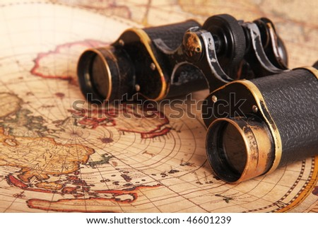 Old binoculars on antique map. Shallow depth of field