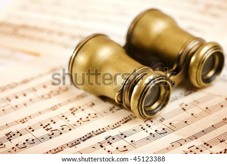 old binoculars on music notes sheet