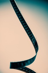 Old black and white 16mm film strip hanging vertically on a light background. For your design.
