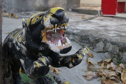 Old black and yellow tiger or panther statue at a Chinese Buddhist temple