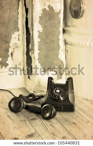 Old black bakelite phone on the floor in a grungy house with the receiver off.
