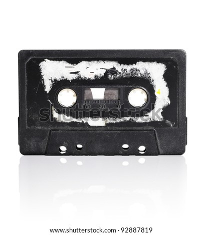 Old black compact audio cassette with torn label isolated on white with natural reflection.