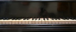 Old black grand piano keyboard with keys from ivory and ebony, part of a musical instrument in panoramic format, copy space, selected focus, narrow depth of field