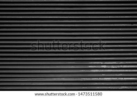 Old black grunge background. Striped wallpaper. Metal wall