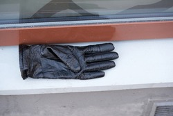 Old black leather gloves lie on a stone
