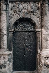 Old black metal door. Fragment of the Boim chapel in Lviv, Ukraine. Old Renaissance architecture, reliefs and sculptures of lions, decorative details and elements close-up.