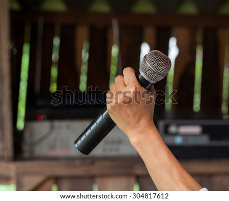Old black microphone in hand, combined with the party.