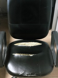 Old black office chair. Vintage leather chair with sponges out. Old and damaged furniture.