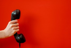 Old black Phone in a hand on a red background