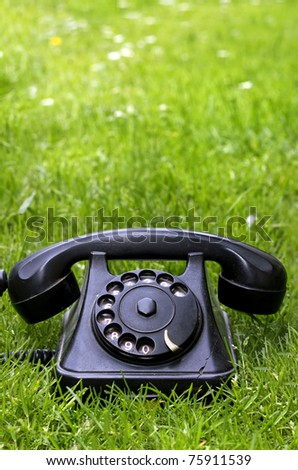 Old black phone in green grass