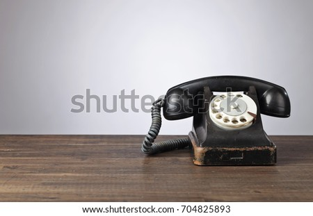 Old black phone on a wooden table. Copy space for your text . #704825893