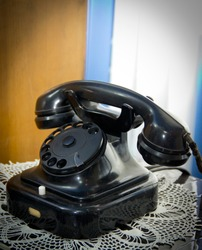 old black phone with a rotary dialer
