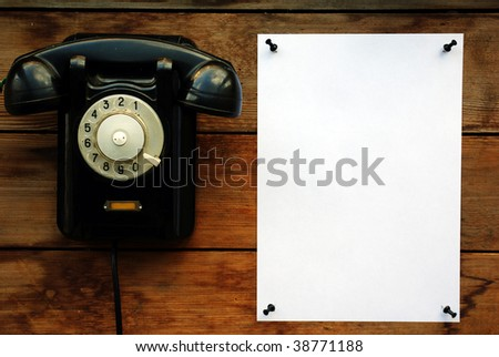 Old black rotary phone and white paper. - stock photo