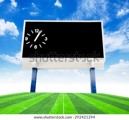 Old black score board in field soccer with blue sky view from stadium.