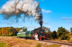Old black steam train with green cars and much smoke. Vintage locomotive with historical tour. Railway in green and yellow autumn forest. top image from golden railroad times. Beautiful countryside