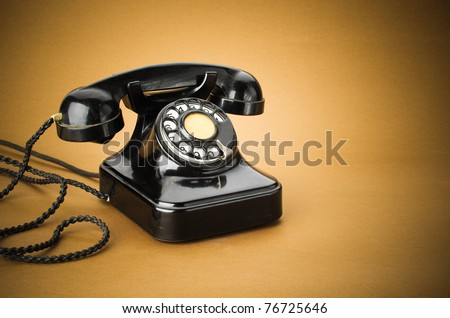old black telephone with rotary disc on brown background