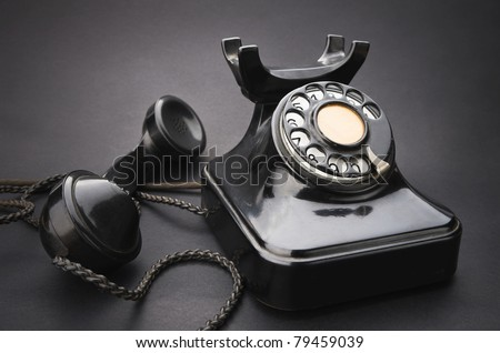 old black telephone with rotary disc on gray background
