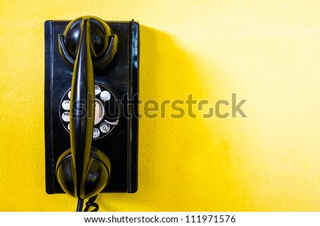 old black telephone with rotary disc on Yellow wall