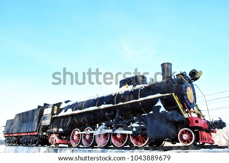 Old black train with red elements covered with snow, standing on platform against blue sky background,  side view of locomotive and railway carriage, Kharkiv, Ukraine #1043889679