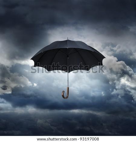 Old black umbrella against rainy sky.