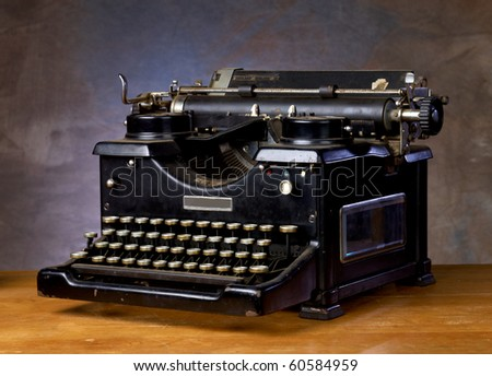 Old black vintage typewriter on a wood counter with neutral background