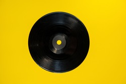 old black vinyl disc lies on a yellow background. Web banner.