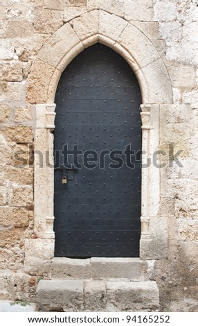Old black wooden medieval door on limestone wall with antique sliding door bolt and padlock.