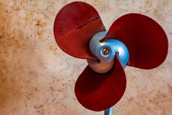 Old blades of the table portable vintage fan. Close up of the retro soviet electric ventilator on a beige background (with empty space), used for cooling on hot days. Antique collectible object.