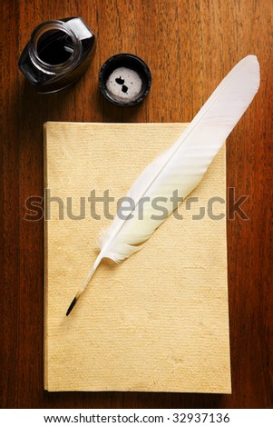 Old blank paper with quill pen and ink on wooden table - stock photo