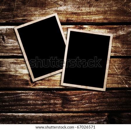 Old blank photos frames lying on a wood surface for text and photo
