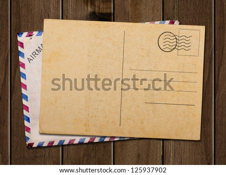Old blank post card and envelope, on wooden table.