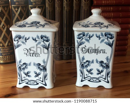 Old blue and white pottery storage jars for rice and pearl barley with German titles for Reis and Graupen on a wooden kitchen table #1190088715