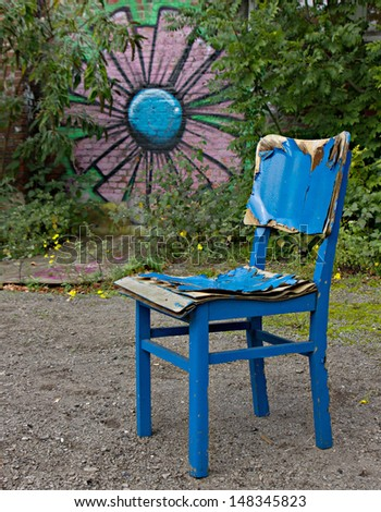 Old blue chair in the open air surrounded by green and graffiti